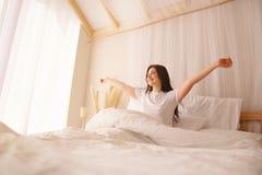 Женщина будя протягивать в кровати в раннем утре стоковые фото