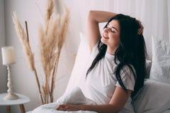Женщина будя протягивать в кровати в раннем утре стоковое фото