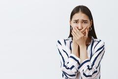 Женщина быть изведенные испуганными сказать любое Вспугнутая тревоженая подруга в striped блузке и ультрамодных серьгах, покрывая стоковые изображения