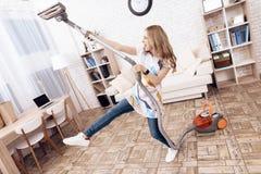 Женщина вакуумирует квартиру Молодая женщина околпачивает вокруг с пылесосом стоковые изображения