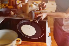 Женщина варит блинчики в кухне Жарить процесс Стоковое фото RF