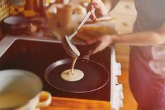 Женщина варит блинчики в кухне sunlight Стоковые Фотографии RF