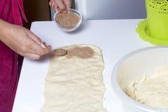 Женщина варит плюшки с циннамоном Она свертывает заполнять на свернутое тесто Смешанные сахар и циннамон Стоковые Изображения RF