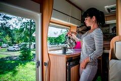 Женщина варя в туристе, motorhome внутреннем RV Стоковое Изображение RF