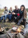 Женщина варя еду на лагерном костере с друзьями в предпосылке Стоковая Фотография RF