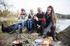 Женщина варя еду на лагерном костере с друзьями в предпосылке Стоковое Изображение RF