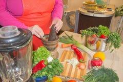 Женщина варя здоровую еду в кухне Варящ здоровую еду дома Стоковые Изображения