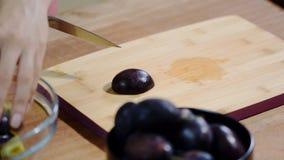 Женщина варя и режа сливу на деревянной разделочной доске подготовлять еды здоровый сток-видео