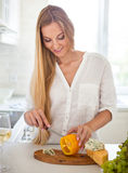 Женщина варя салат овощей на кухне Стоковое Фото