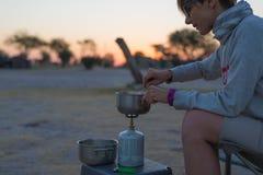 Женщина варя с газовой плитой в месте для лагеря на сумраке Газовая горелка, бак и дым от кипятка Приключения в африканском сооте стоковая фотография rf