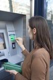Женщина кладя карточку в ATM весной стоковые фотографии rf