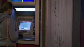 Женщина вводя карточку банка в ATM для того чтобы получить наличные деньги сток-видео