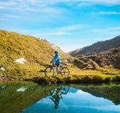 Женщина велосипедиста в mountais высоты Стоковая Фотография