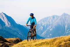Женщина велосипедиста в mountais высоты Стоковая Фотография RF