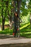 Женщина велосипедиста ехать велосипед в парке Стоковая Фотография RF
