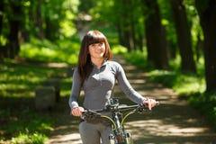 Женщина велосипедиста ехать велосипед в парке Стоковые Фотографии RF