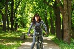 Женщина велосипедиста ехать велосипед в парке Стоковое Фото