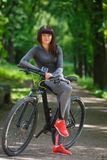 Женщина велосипедиста ехать велосипед в парке Стоковое Изображение RF