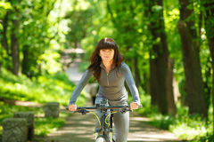 Женщина велосипедиста ехать велосипед в парке Стоковое фото RF