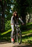 Женщина велосипедиста ехать велосипед в парке Стоковая Фотография