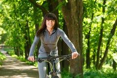 Женщина велосипедиста ехать велосипед в парке Стоковые Фото