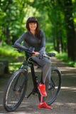 Женщина велосипедиста ехать велосипед в парке Стоковое Изображение