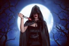 Женщина ведьмы хеллоуина в ноче с noonlight с backg тумана Стоковые Фото
