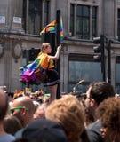 Женщина взбирается вверх светофор на цирке Оксфорда, Лондоне, для того чтобы получить лучший взгляд парада гей-парада стоковые изображения rf
