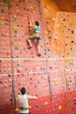 Женщина взбираясь вверх стена утеса Стоковое Изображение RF