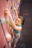 Женщина взбираясь вверх стена утеса Стоковые Фото