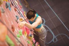 Женщина взбираясь вверх стена утеса Стоковые Изображения