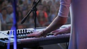 Женщина взгляда задней стороны замедленного движения играет музыку на концерте