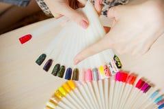 Женщина взгляд сверху выбирает желтый маникюр шеллака цвета Техник ногтя показывает цветовую палитру обслуживаний ногтя в салоне  стоковые фотографии rf