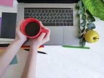 Женщина взгляд сверху настольного компьютера вручает работе белую деревянную дизайнерскую кофейную чашку стоковые фотографии rf