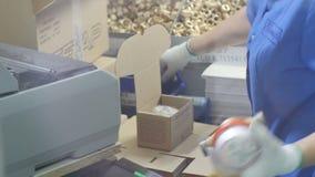 Женщина взгляда со стороны Timelapse упаковывает метры в коробках сток-видео