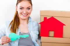Женщина двигая внутри с коробками и бумажным ключом дома стоковая фотография rf