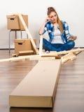 Женщина двигая в держать винты и части мебели стоковая фотография rf