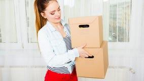 Женщина двигая в коробки нося многоквартирного дома стоковая фотография rf