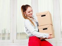 Женщина двигая в коробки нося многоквартирного дома стоковое фото