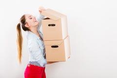 Женщина двигая в коробки нося многоквартирного дома стоковая фотография