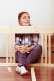 Женщина двигая в мебель собрания на новом доме Стоковые Фотографии RF