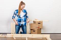 Женщина двигая в мебель собрания на новом доме Стоковые Изображения RF