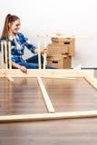 Женщина двигая в мебель собрания на новом доме Стоковая Фотография RF