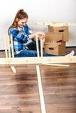 Женщина двигая в мебель собрания на новом доме Стоковая Фотография