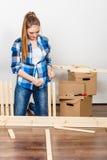 Женщина двигая в мебель собрания на новом доме Стоковые Фото