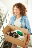 Женщина двигая в новую домашнюю коробку нося вверх Стоковое фото RF