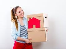 Женщина двигая в дом с коробками и бумажным домом стоковые изображения rf