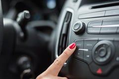 Женщина включая автомобильный радиоприемник стоковая фотография rf