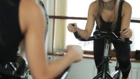 Женщина включена на неподвижном велосипеде, сжимающ handlebar с вашими руками и касающими местами акции видеоматериалы