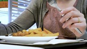 Женщина внутри ресторана еды есть французские фрикадельки картофеля фри сток-видео